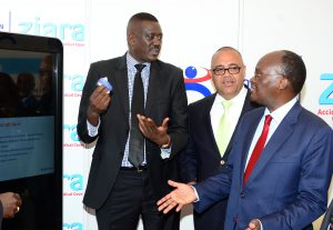 The Cabinet Secretary for Transport, Infrastructure, Housing & Urban Development James Macharia (right)  is taken through the features of the Resolution Ziara Plan by Resolution Insurance Group CEO Peter Nduati (left) during the launch of an accident emergency medical cover for commuters in Public Service Vehicles (PSV). Looking on is Matatu Owners Association Chairman Simon Kimutai